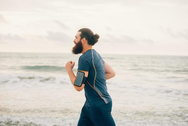 Der bärtige hipster-mann läuft an einem bewölkten tag am strand in der nähe von meer oder ozean.