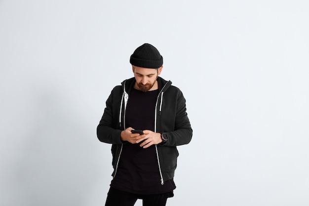 Der bärtige junge mann in schwarzer und dunkelblauer freizeitkleidung schaut in sein smartphone, das auf weiß isoliert ist
