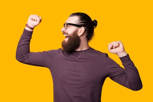Der bärtige junge mann mit brille schaut mit beiden händen nach oben aufgeregt zur seite