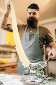 Der bärtige koch in der schürze arbeitet mit teig in der nudelmaschine auf dem hölzernen küchentisch. selbst gemachter spaghetti-kochprozess