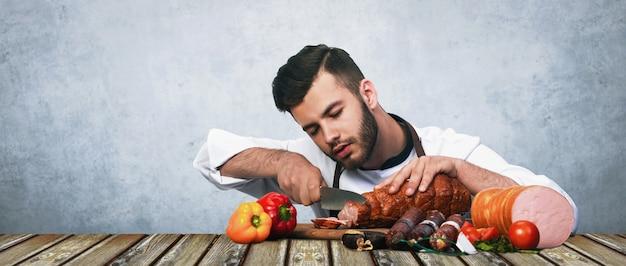 Der bärtige koch schneidet fleisch auf dem tisch