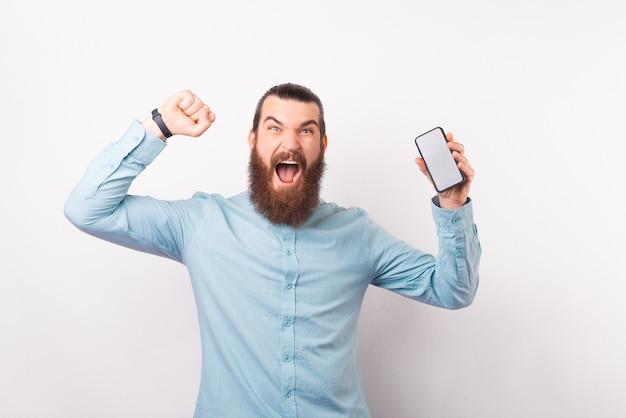 Der bärtige mann feiert den sieg, während er sein telefon hält.