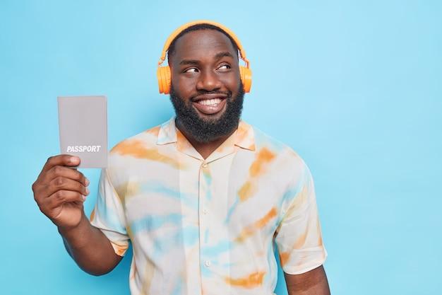 Der bärtige mann hat einen fröhlichen ausdruck, hört musik über kopfhörer und hält einen reisepass für eine reise ins ausland, nachdem er ein visum erhalten hat, sieht positiv aus und posiert gegen die blaue wand