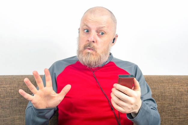 Der bärtige mann hört gerne seine lieblingsmusik über einen audioplayer in kleinen kopfhörern.