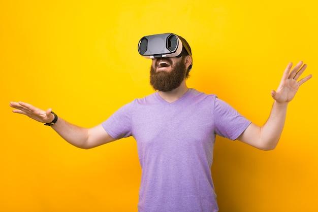 Der bärtige mann probiert sein vr-headset in einem studio auf gelbem hintergrund aus.