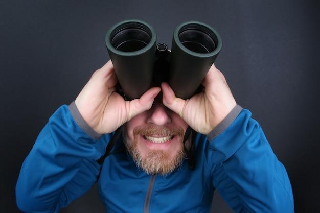 Der bärtige mann schaut durch ein fernglas auf grauem hintergrund auf