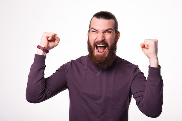 Der bärtige mann schaut in die kamera und schreit mit beiden händen, weil er gewonnen hat