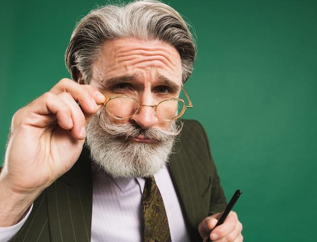 Der bärtige und schnurrbärtige lehrer mittleren alters im anzug hält die hand mit der brille und schaut auf eine grüne wand