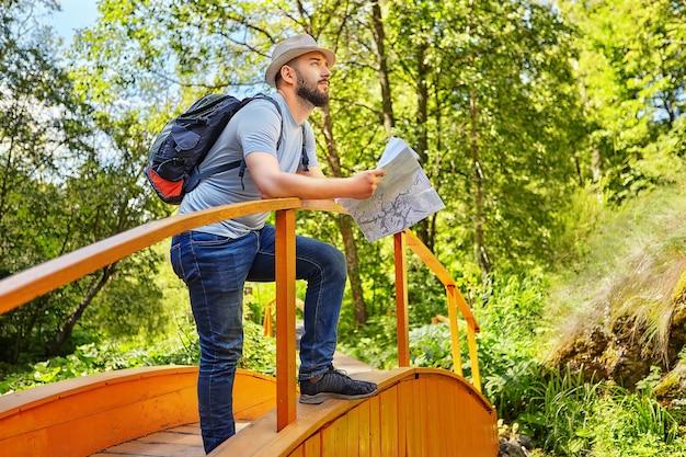 Der bärtige wanderer mit hut steht auf einer holzbrücke und hält eine karte des gebiets, in dem er an einem sonnigen sommertag durch das gebiet geführt wird.