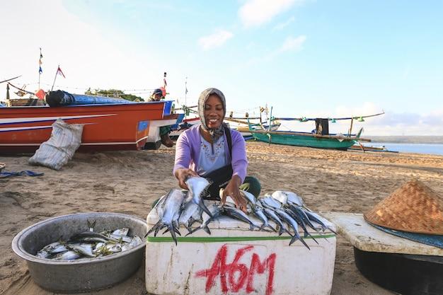 Der balinesische fischhändler verkauft fisch auf dem morgenmarkt in bali