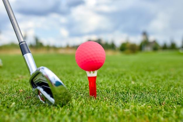 Der ball am loch auf dem golfplatz. golfkonzept. nahaufnahme eines golfballs auf grünem gras neben einem golfschläger vor einem treffer.