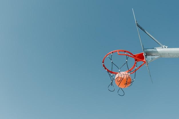 Der ball fliegt in den reifen auf einem basketballplatz im freien in einem öffentlichen park.