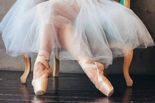 Der ballerina-balletttänzer im tutu-rock und im pointe shous, der auf dem klassischen stuhl sitzt