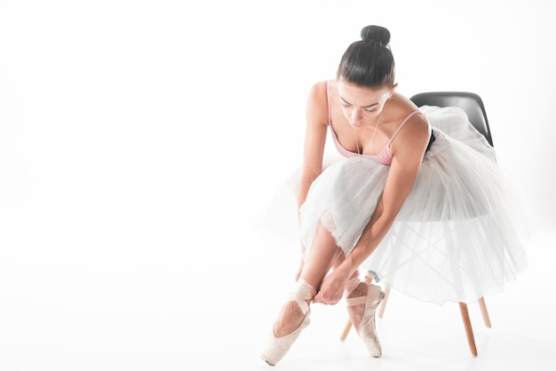 Der balletttänzer, der auf stuhl sitzt, binden oben ihre pointe schuhe gegen weißen hintergrund