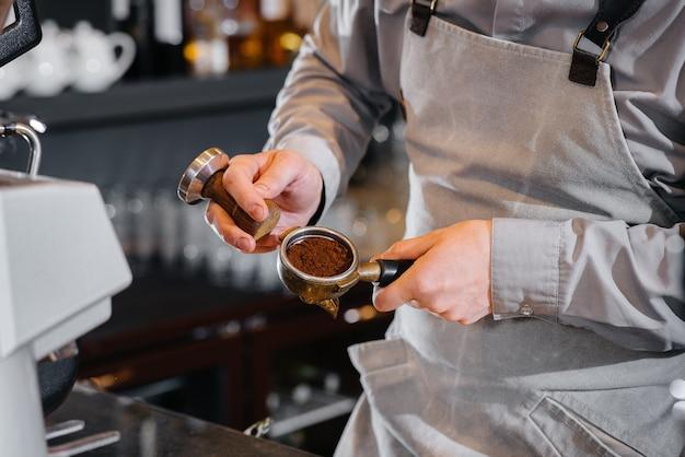 Der barista bereitet köstlichen kaffee in einer modernen coffeeshop-nahaufnahme zu.