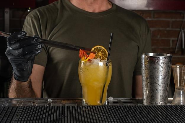 Der barkeeper an der bar macht einen alkoholischen cocktail mit eis und orange.