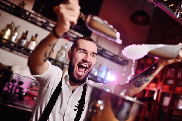 Der barkeeper auf einer party in einem nachtclub gießt eis für cocktails ein und schreit glücklich gegen die bar