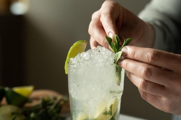 Der barkeeper aus der nähe bereitet einen mojito-cocktail an der bar zu. ein mann dekoriert einen mojito-cocktail mit minze und limette