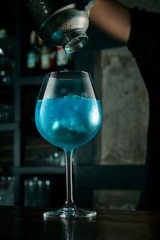 Der barkeeper bereitet einen alkoholischen cocktail zu