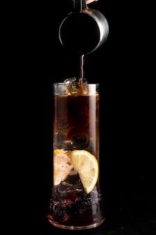 Der barkeeper bereitet einen blackberry espresso tonic cocktail zu und gießt kaffee hinein.