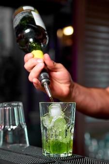 Der barkeeper bereitet im nachtclub kalte cocktails zu.