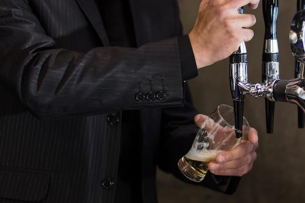 Der barkeeper, der ein bier brät