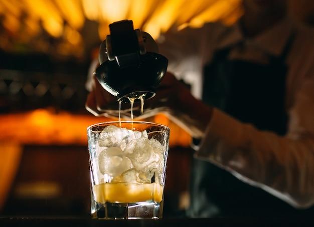 Der barkeeper drückt zitronensaft in einen cocktail