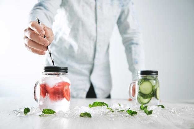 Der barkeeper legt gestreiftes trinkhalm in ein glas mit frischer, kalter, hausgemachter limonade aus eis, erdbeere, zerschlagenem geschmolzenem eis und gurken-minz-limonade in ein anderes glas auf der rückseite.