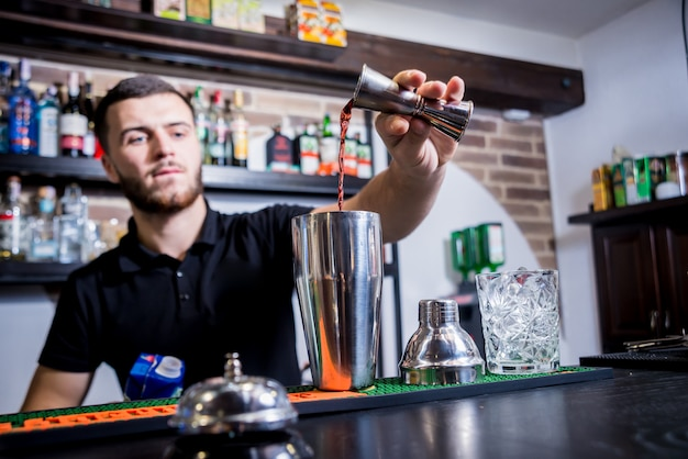 Der barkeeper macht an der theke einen alkoholfreien cocktail. frische cocktails. barmann bei der arbeit. nachtleben.