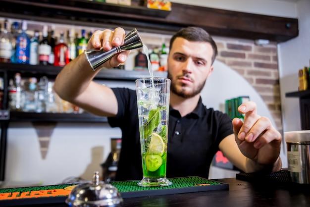 Der barkeeper macht an der theke einen alkoholfreien cocktail. frische cocktails. barmann bei der arbeit. restaurant. nachtleben.