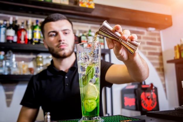 Der barkeeper macht an der theke einen alkoholfreien cocktail. frische cocktails. barmann bei der arbeit. restaurant.