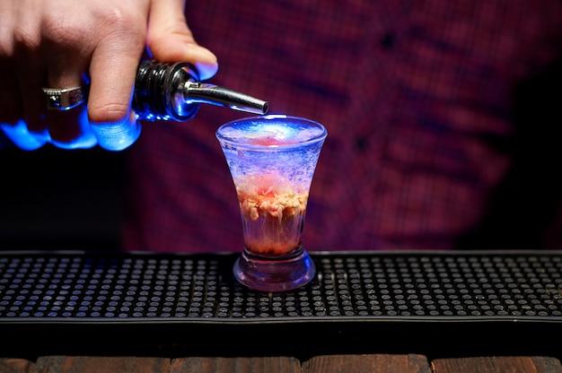 Der barkeeper macht einen alkoholischen schuss in einem kleinen glas.