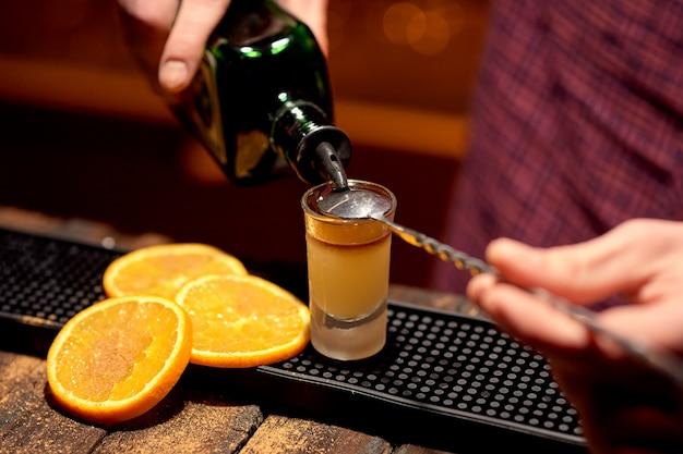 Der barkeeper macht einen alkoholischen schuss mit einer mit zimt bestreuten vorspeise aus orange.