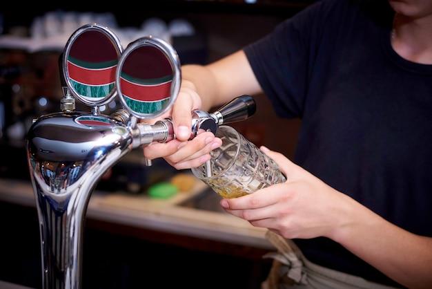 Der barkeeper schüttet bier aus dem wasserhahn in den becher.