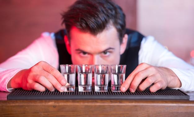 Der barkeeper stellt die gläser genau hintereinander in die theke.