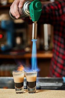 Der barkeeper zündet das alkoholische getränk mit einem gasbrenner an