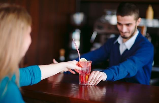 Der barmann gibt dem mädchen den cocktail.