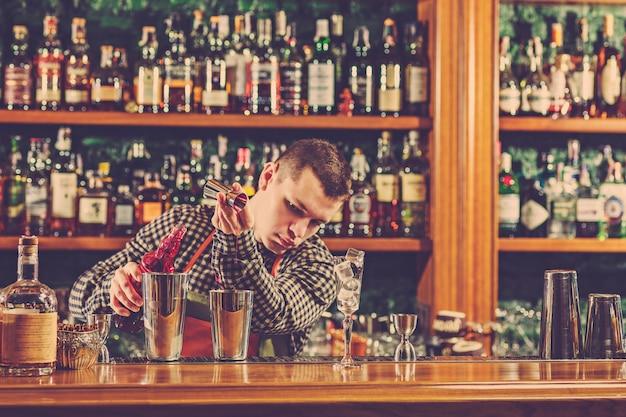 Der barmann macht einen alkoholischen cocktail an der theke in der bar