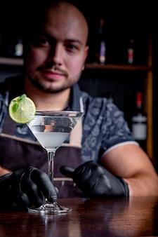 Der barmann serviert dem kunden an der bar im restaurant cocktails. herzlich willkommen