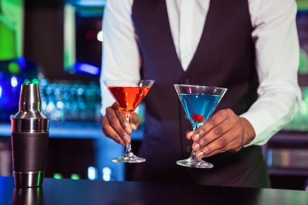 Der barmixer, der blaues und orange cocktail dient, trinkt am barzähler in der bar