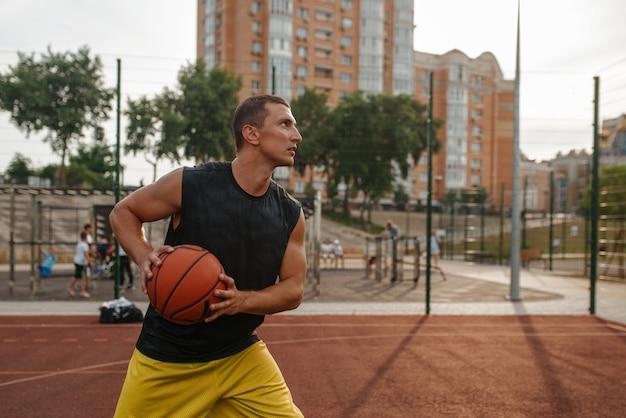 Der basketballspieler bereitet sich auf ein shooting auf dem platz im freien vor.