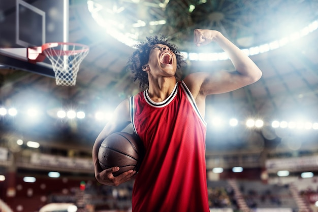 Der basketballspieler gewinnt das spiel im korbstadion voller zuschauer.