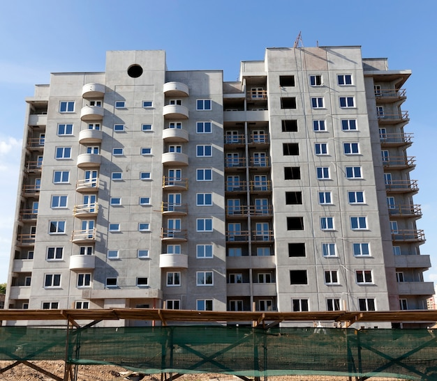 Der bau eines mehrstöckigen gebäudes aus standardblöcken aus beton. wohnungen für menschen, die in einem neuen stadtteil leben