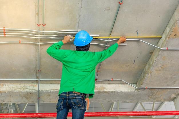 Der bauarbeiter, der mit elektrischem verteilungssystem der metallrohre misst