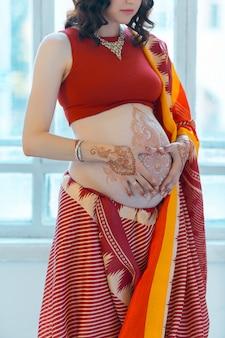 Der bauch der schwangeren frau mit henna-tätowierung