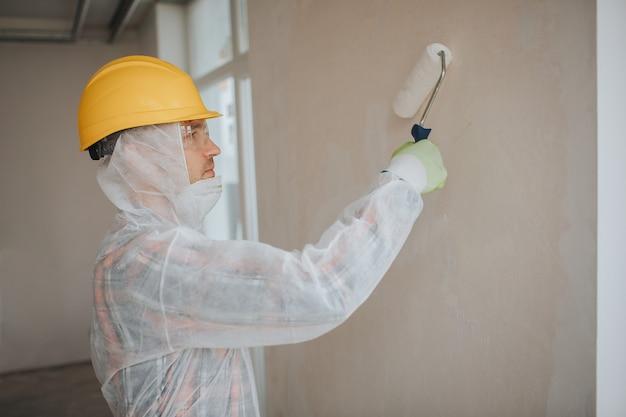 Der bauherr arbeitet auf der baustelle. arbeiter mit einem farbroller. er trägt einen schutzanzug und eine maske für ein gesicht