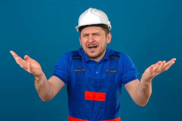 Der bauherr, der eine bauuniform und einen streitenden sicherheitshelm trägt, hat einen streit, der die hände in bestürzter achselzucken hebt und mit dem verärgerten, gestörten gesicht über dem isolierten blau verwechselt
