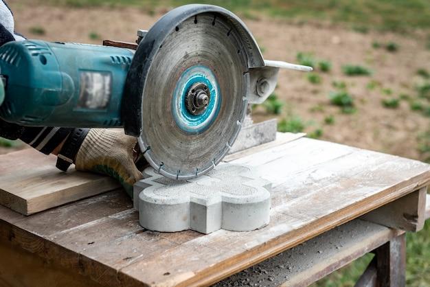 Der bauherr schneidet die pflasterplatte mit einer elektrischen säge.