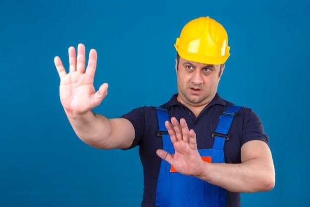 Der baumeister, der eine bauuniform und einen schutzhelm trägt und seine hände hochhält, sagt, dass er über eine isolierte blaue wand nicht näher kommt