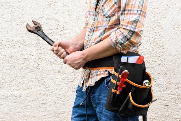 Der baumeister hält einen schraubenschlüssel in der hand